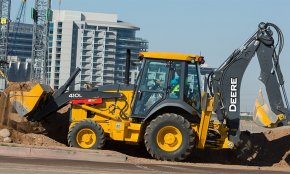 A 410L Backhoe Loader works with an apartment complex in the background