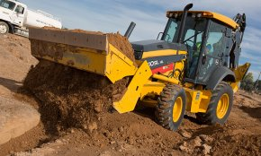 A backhoe loader unloads a bucket of dirt
