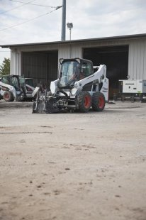 Bobcat planer attachment mounted to a skid-steer loader cuts an asphalt parking lot.