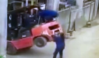 The woman jumps on the back of the forklift to pull it back down as it starts to tip